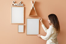 Woman Hanging Blank Photo Frames On Wall