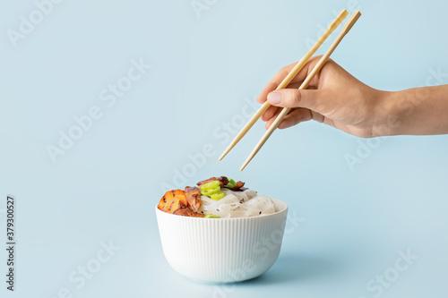 Fototapeta Woman eating tasty rice noodles on color background obraz