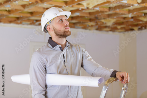 Fototapeta builder with a paper on the ladder obraz