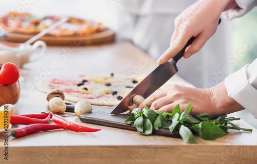 Obraz na plátně Chef making tasty pizza in kitchen, closeup