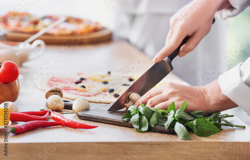 Chef making tasty pizza in kitchen, closeup