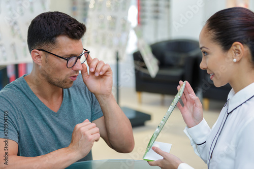 Fotografie, Obraz man trying on spectacles and looking in mirror