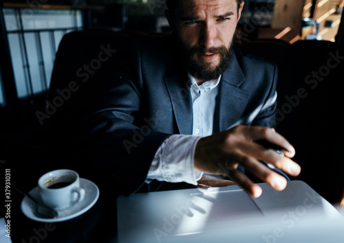 business man in suit in cafe in front of laptop with a cup of drink official Canvas Print