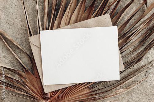 Summer stationery still life. Closeup of blank card mock-up and craft envelope on dry palm leaf. Grunge beige concrete background. Flat lay, top view. Tropical vacation concept. Moody boho design. - 379310717