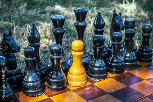 Fotografía White chess pawn standing with black pieces on the chessboard