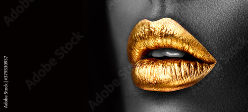 Golden lipstick closeup. Gold metal lips. Beautiful makeup. Sexy lips, bright lip gloss paint on beauty model girl's mouth, close-up. Lipstick. Black and white image