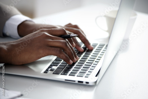 Foto Close-up of hands of african american businessman typing on a keyboard