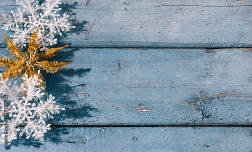 Fototapeta Wooden Christmas background, top view. Place for text on a new year's background. Beautiful blue Christmas horizontal background with white snowflakes and Golden shiny star. obraz