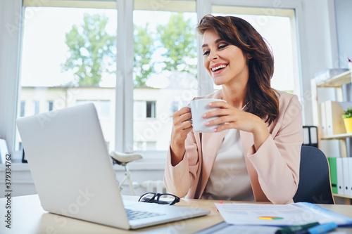 Fototapeta Happy woman working from home, drinking coffee obraz