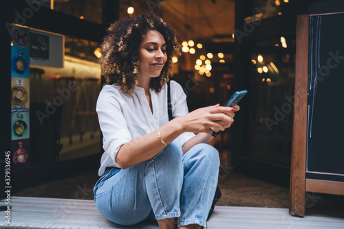 Fotografia, Obraz Smiling young woman browsing smartphone in cafe