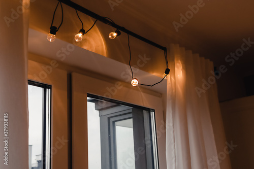 Fototapeta Illumination lights, garland light set for Christmas and New Year's Day  .atmosphere. Lanterns that hang on a single wire and shine with a soft, warm light on the window obraz
