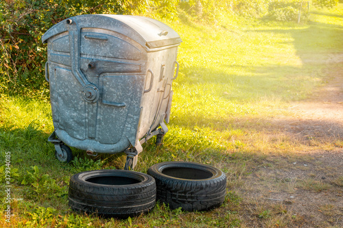 Fototapeta Used car tires left beside the garbage container obraz