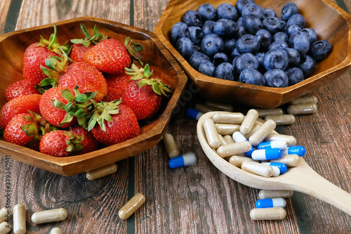 Fototapeta fresh natural fruits vs pills. Natural vitamin in fruits vs synthetic vitamin in pills. Choice between natural and synthetic way of health care. Alternative medicine. Dietary supplement obraz