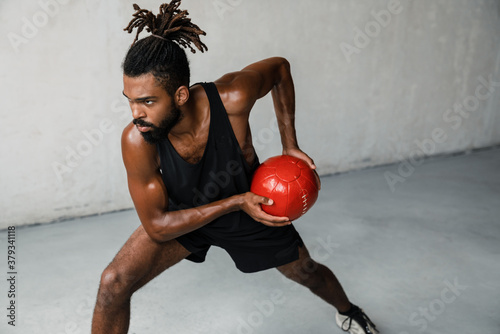 Image of african american sportsman working out with medicine ball Fototapeta