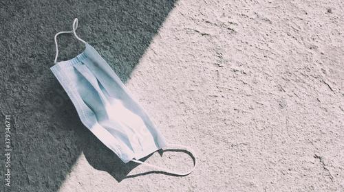 Fototapeta Used face mask lying on the concrete floor in the street obraz