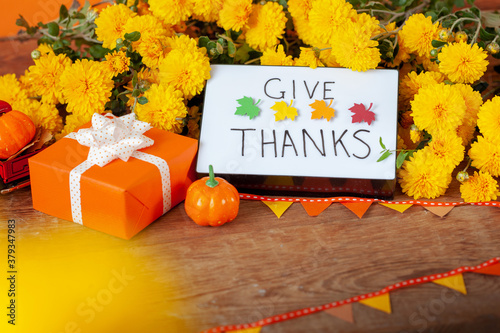 Creative orange gift box. Thanksgiving autumn composition with yellow flower. Lightbox with the phrase Give thanks.
