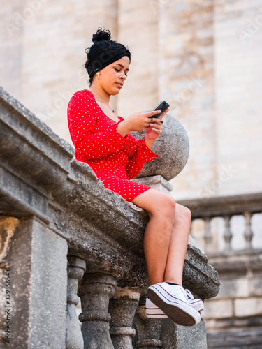 Cuadros en Lienzo An attractive young female looking at her smartphone while sitting on a stone ba