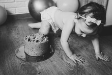 Little Girl With Cake On Floor. Smash Cake. Funny Toddler Eating Cake. First Birthday On Background Balloons. Black And White Photo.