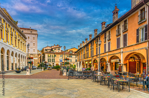 Typical italian buildings and tables of street restaurants on Piazza del Mercato Market square in Brescia city historical centre, evening twilight view, Italian street, Lombardy, Northern Italy