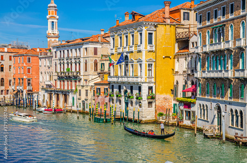 Grand Canal waterway in Venice historical city centre with sailing gondola, Palazzo Civran palace, colorful buildings and Church Holy Apostles of Christ bell tower Canvas Print