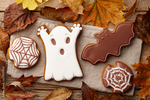 Fototapeta Halloween gingerbread cookies on wooden table with autumn leaves obraz