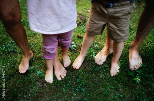 Obraz na plátně Bare feet of family with small children standing barefoot outdoors in nature, grounding concept