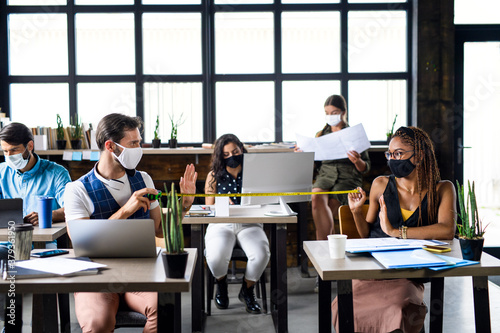 Business people with face masks in office, coronavirus and safe distance concept.