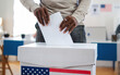 Leinwandbild Motiv Unrecognizable african-american man putting his vote in the ballot box, usa elections and coronavirus.