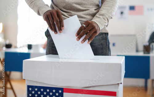 Unrecognizable african-american man putting his vote in the ballot box, usa elections and coronavirus.