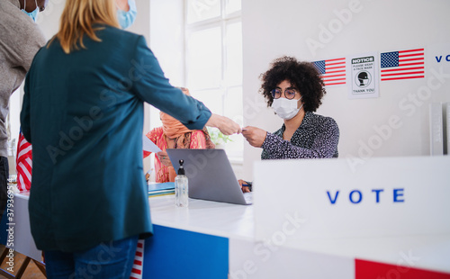 People with face mask voting in polling place, usa elections and coronavirus. - 379369514
