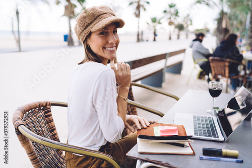 Half length portrait of cheerful caucasian female sitting on cafe terrace with l Fototapet