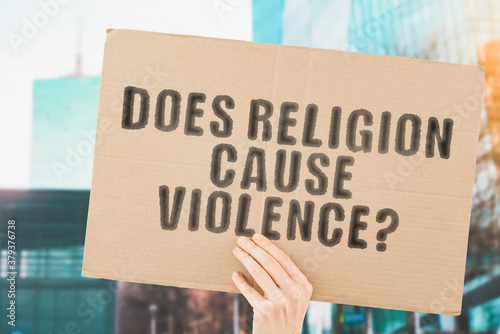 Obraz na plátne The question  Does religion cause violence?  on a banner in men's hand with blurred background