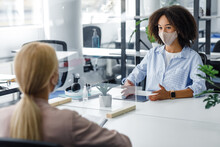 Young Business Workers In Protective Mask Talking To Each Other In Office Through Partition To Prevent COVID-19 Infection