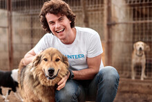 Cheerful Volunteer With Dog In...