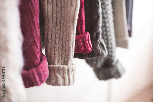 Obraz na plátně Knitted colorful clothes hang on rack indoors in shop