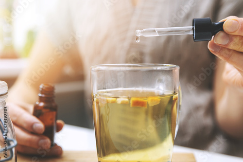 dietary supplements and vitamins - woman adding drops in cup of tea with dropper.