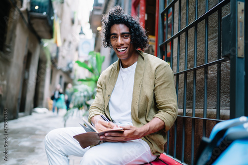 Fototapeta Portrait of cheerful handsome curly male in casual wear enjoying drawing sketches outdoors during free time, smiling young hipster guy 20s creating articles and satisfied with leisure in old city obraz