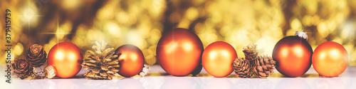 Fototapeta Orange christmas balls and cones in front of golden background obraz