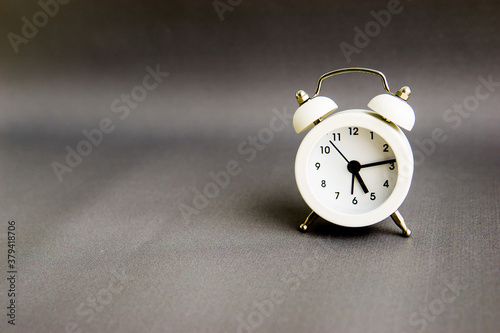White alarm clock on a gray background. Empty space for text. Wallpaper Mural