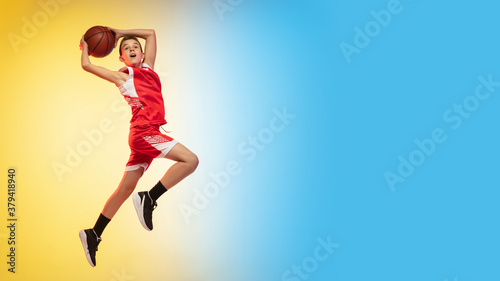 Fototapeta Game. Portrait of young basketball player in uniform on gradient studio background. Teenager confident practicing with ball. Concept of sport, movement, healthy lifestyle, ad, action, motion. Flyer obraz