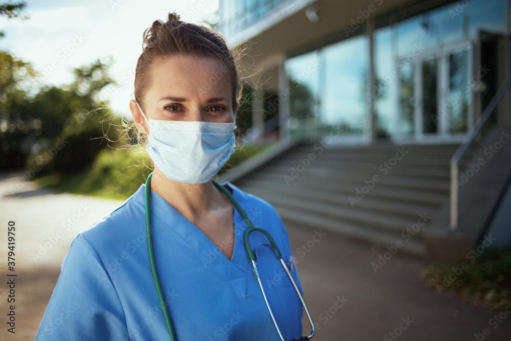 Fototapeta modern physician woman in uniform outside near clinic
