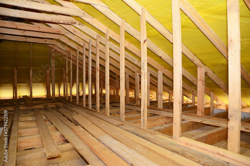 Photo A close-up on an unfinished attic construction with wooden roof beams, planks, rafters, ceiling joists and vapor barrier film inside a new house