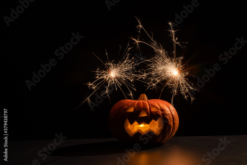 Halloween pumpkin with scary carved grimace and sparklers.