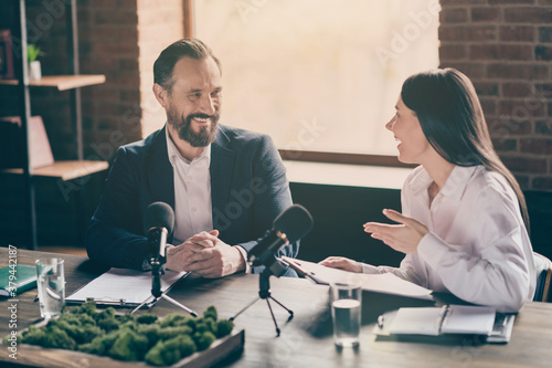 Photo of two business people corporate partners relationship answer journalist press conference questions speak mic education political forum convention sit modern office indoors