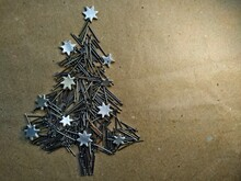 Christmas Tree Folded From Construction Nails Decorated Silver Stars On Kraft Paper Background.