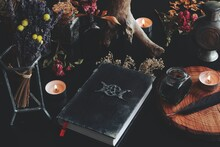 Wiccan Witch Altar With Hand Made Old Looking Book Grimoire With Triple Moon Symbol, And Other Various Items - Dried Flowers, Nature Elements, Burning Candles, Ink Bottle, Feather, In Black Background
