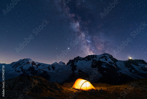 Foto lluminated red tent high in the mountains under the night sky with the milky way