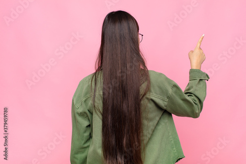 Fototapeta asian young woman standing and pointing to object on copy space, rear view obraz