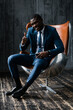 Black male businessman in a classic suit sits in an office chair, smiles and raises his thumb up