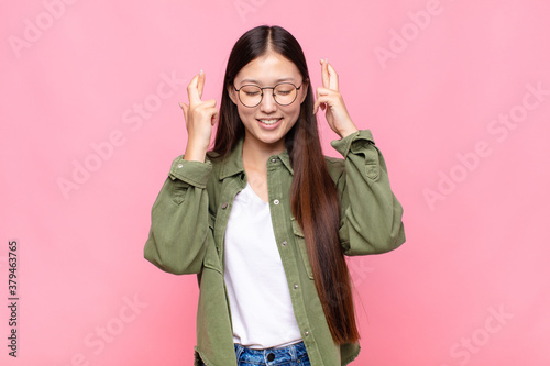 Foto asian young woman smiling and anxiously crossing both fingers, feeling worried a